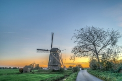 Around the pumping mill Hoekermolen at Nigtevecht (Netherlands) the gold coloured sunset complements the green meadows